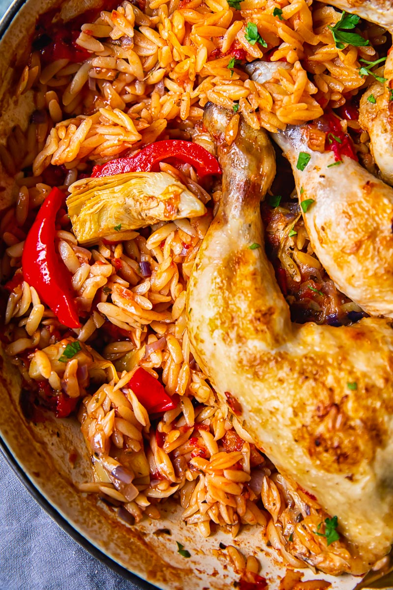 top down view of orzo in a pan with chicken legs.