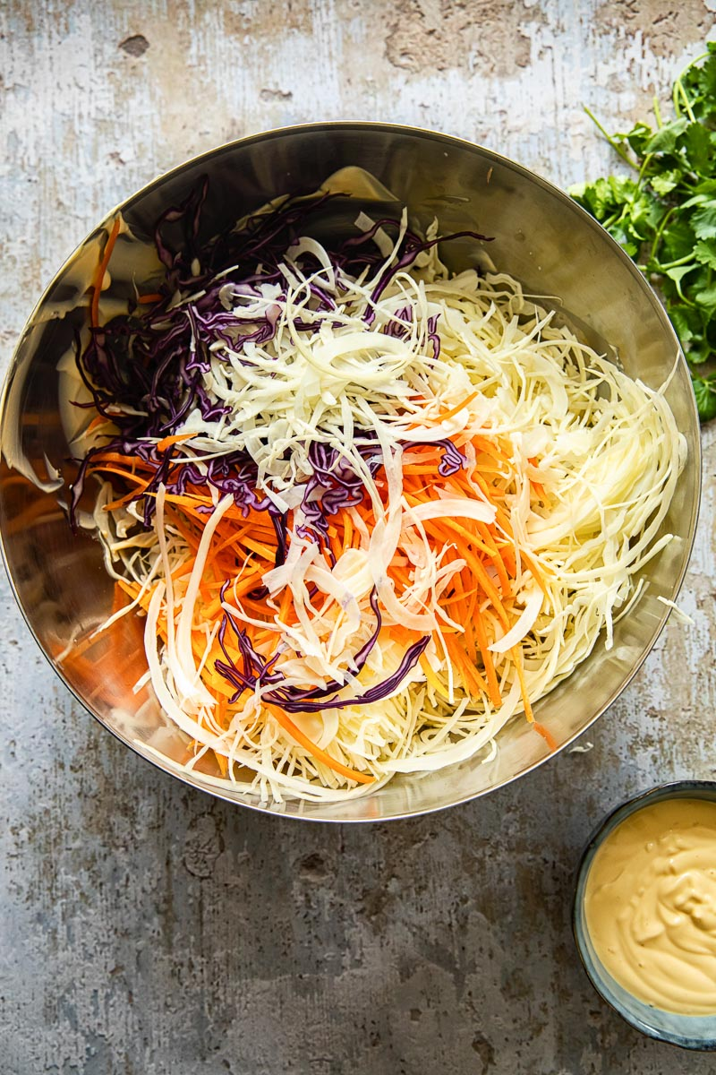 homemade slaw mix in a stainless steel bow, mayonnaise dressing next to it in a small blue bowl.