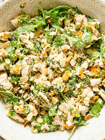 chicken salad with arugula, almonds and apricots in a bowl