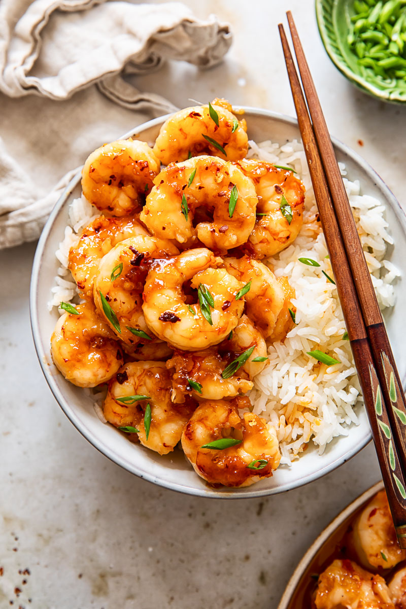 top down view of shrimp on top of rice in a bowl with chopsticks, sliced green onions and a napkin.