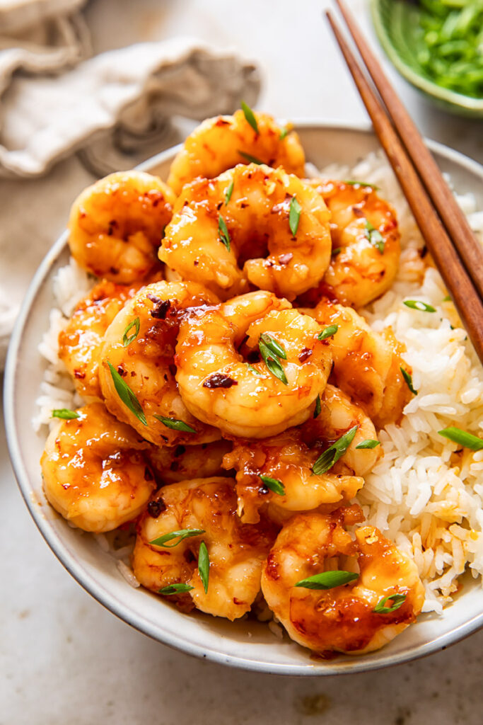 glazed shrimp on top of rice in a bowl.