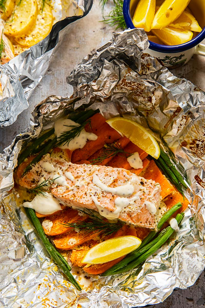 salmon on top of sweet potatoes and green beans in a foil packet.