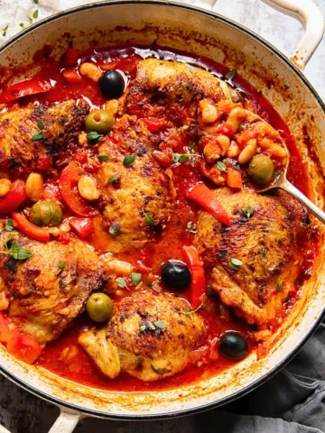 Chicken with red peppers, olives and white beans in a tomato sauce in a pan