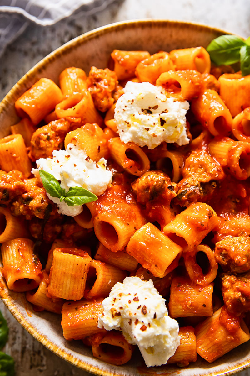 top down view of rigatoni with sausage in tomato sauce topped with ricotta