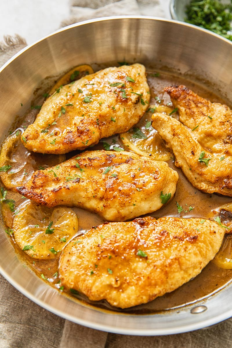top down view of chicken breasts in lemon sauce in a pan