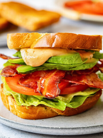 close up of BLT sandwich with avocado and sauce spilling over