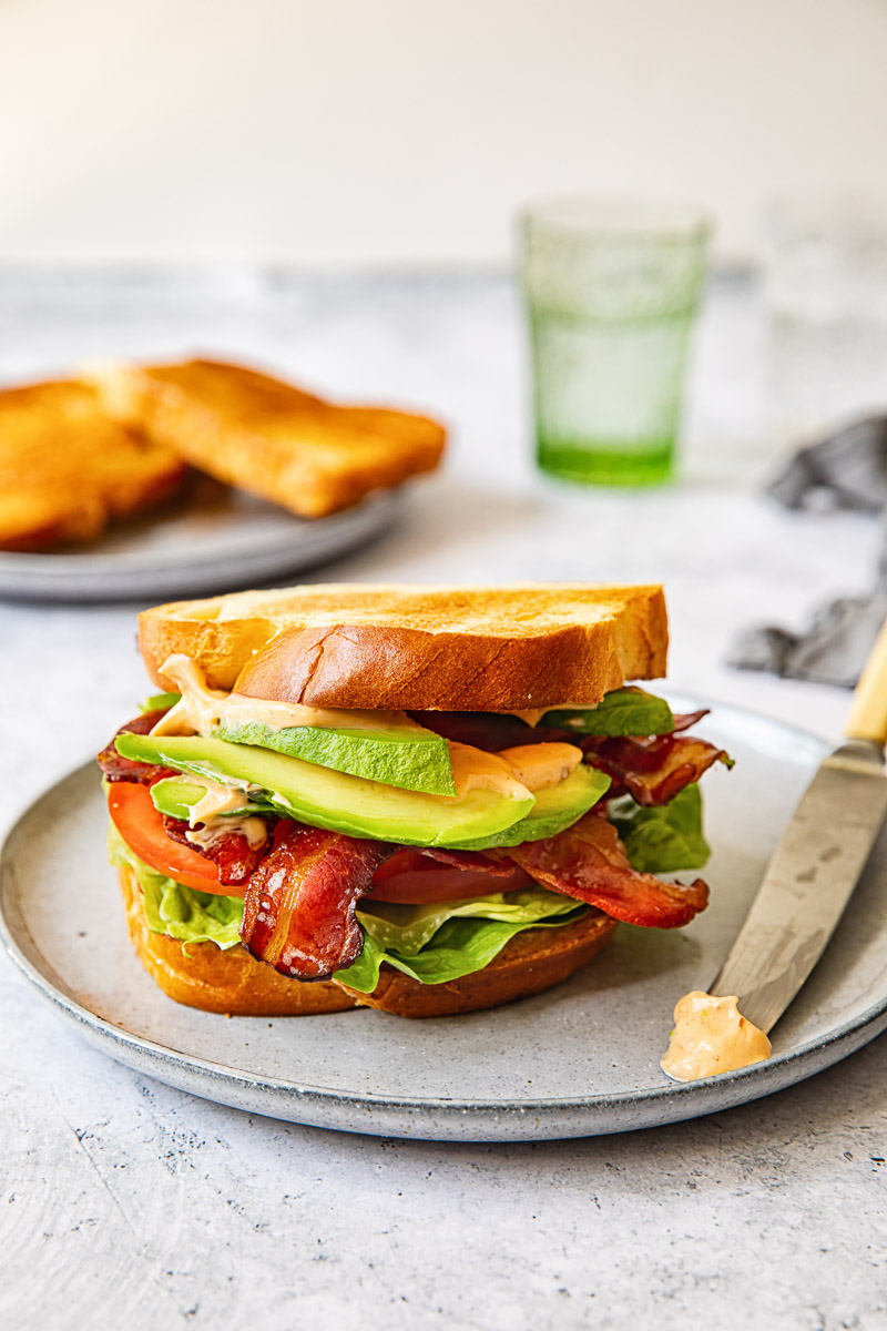 sandwich on grey plate, butter knife on the plate, bread sliced and green water glass in the background.