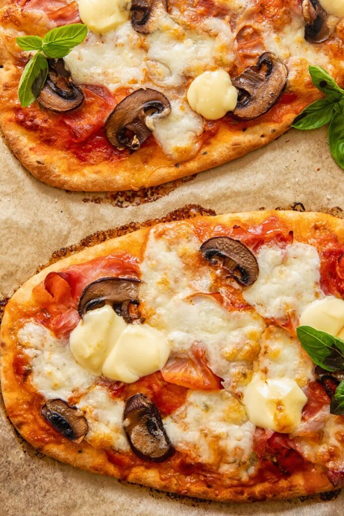 Naan pizza on baking sheet with mushrooms and cheese