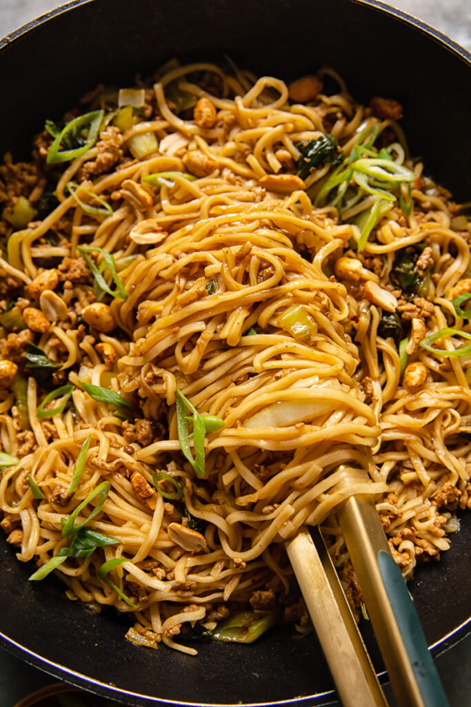 noodles in a black wok with tongs holding the noodles