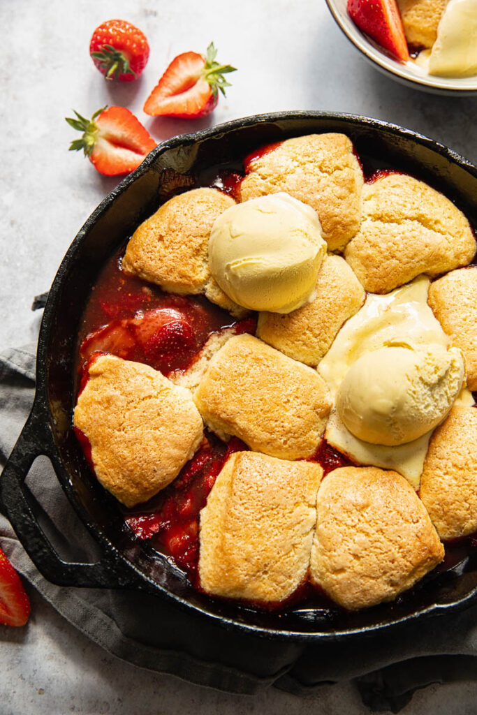 strawberry cobbler in a cast iron skillet, topped with ice cream