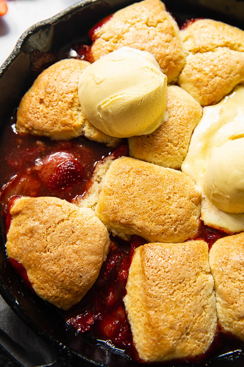 top down view of strawberry cobbler topped with ice cream