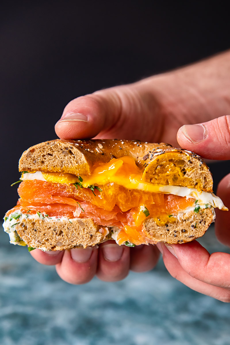 cross section of a bagel sandwich filled with cream cheese, smoked salmon and fried egg