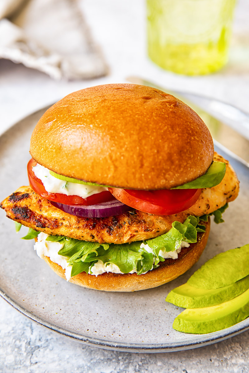 top down view of grilled chicken breast in a bun with lettuce, onion, tomato and avocado
