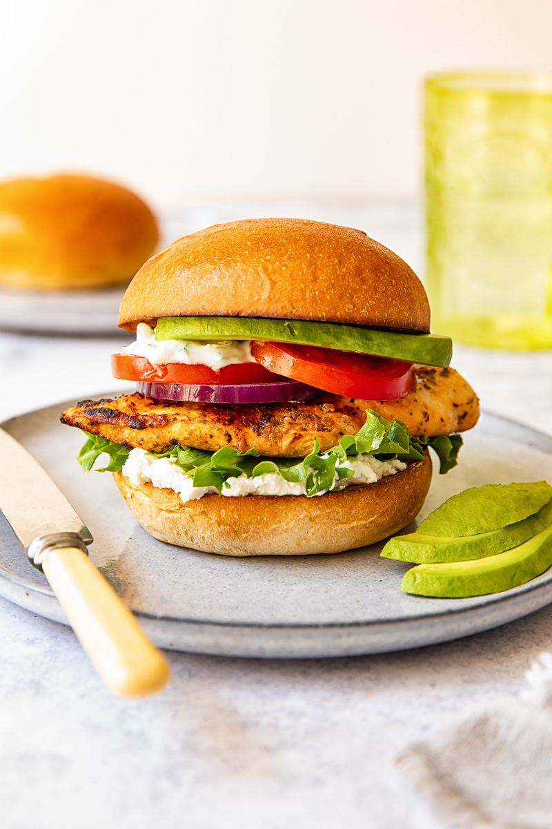 chicken burger on a grey plate, avocado slices, a butter knife, a green glass in the background.