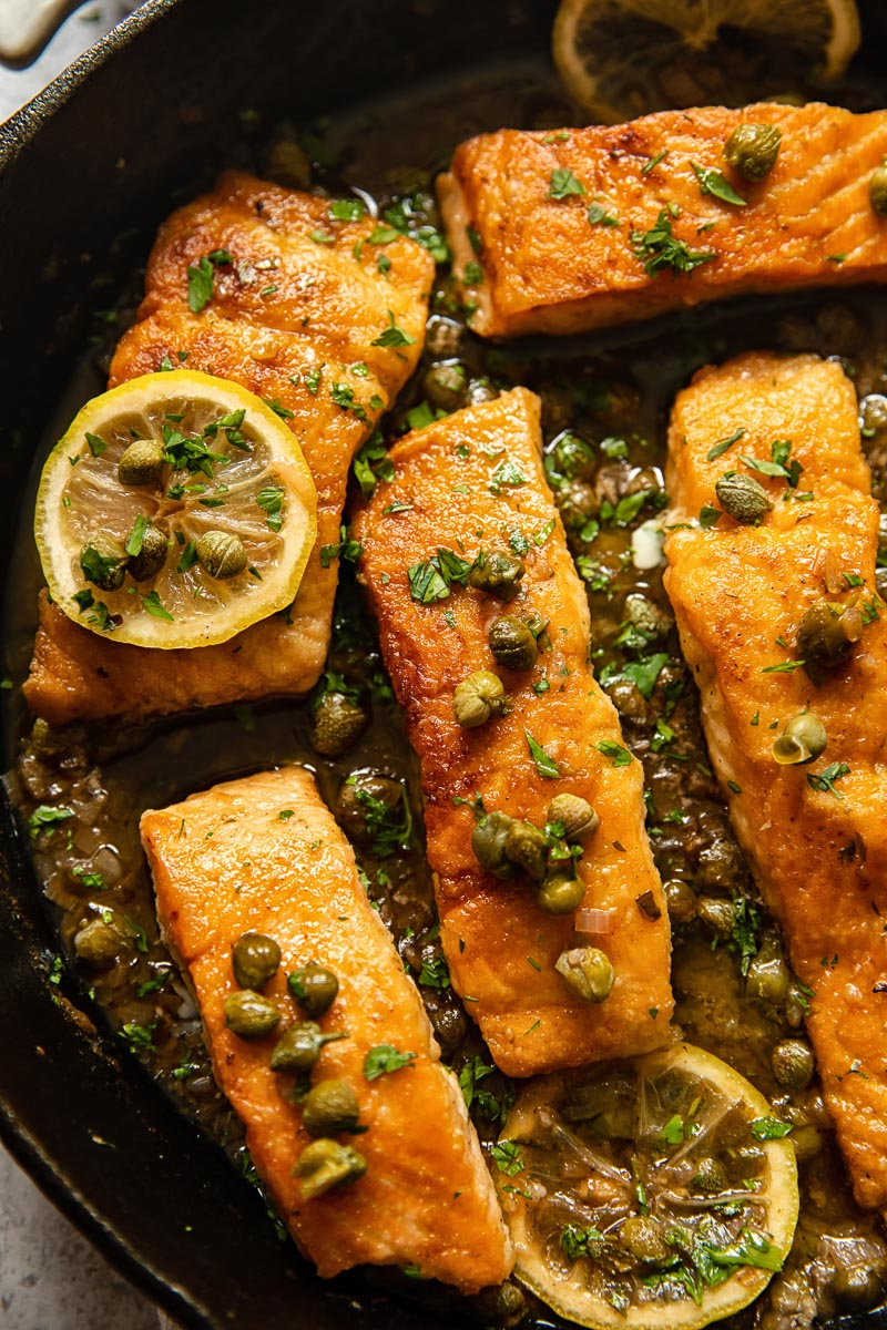close up of salmon piccata in a cast iron pan