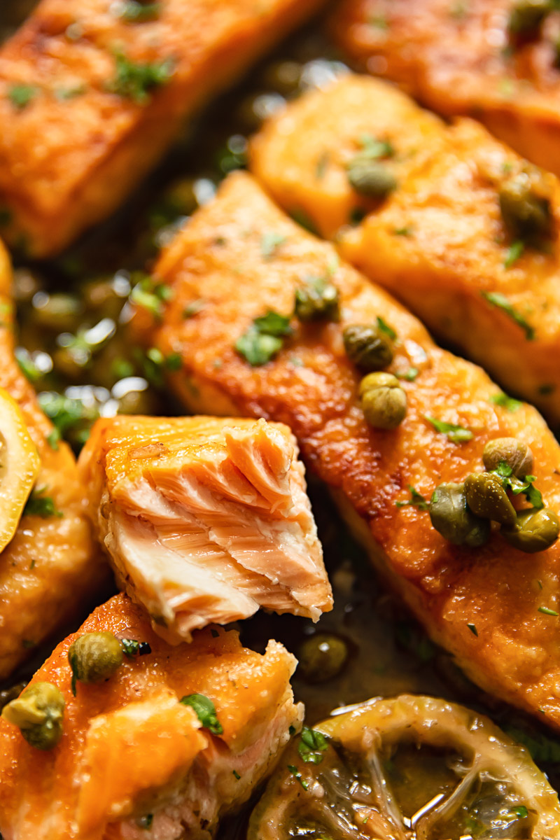 close up of salmon pieces topped with capers and parsley