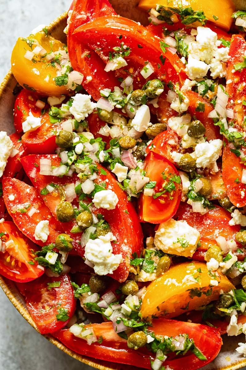 close up of tomato salad with herbs and feta
