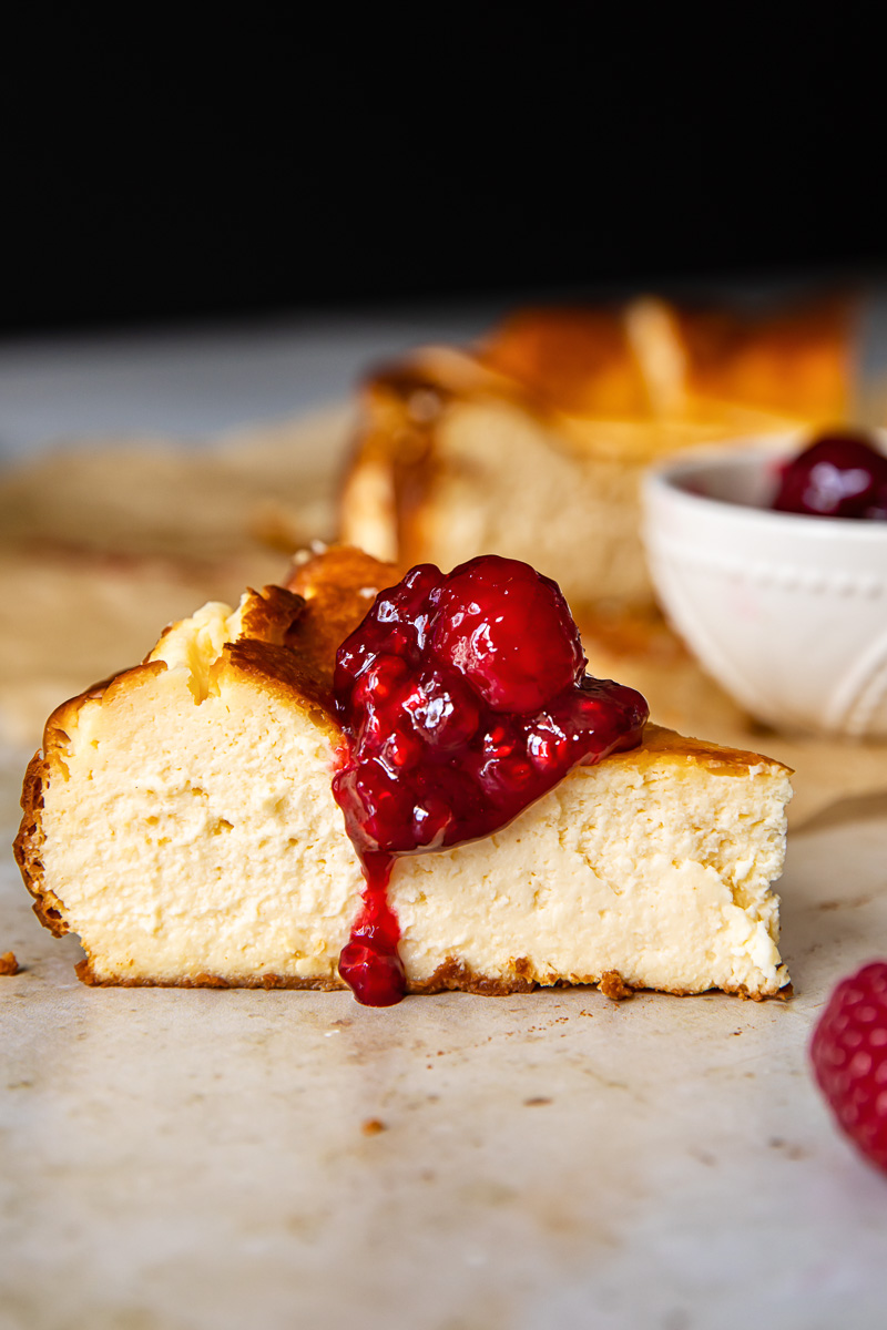 side view of a cheesecake slice with raspberry compote