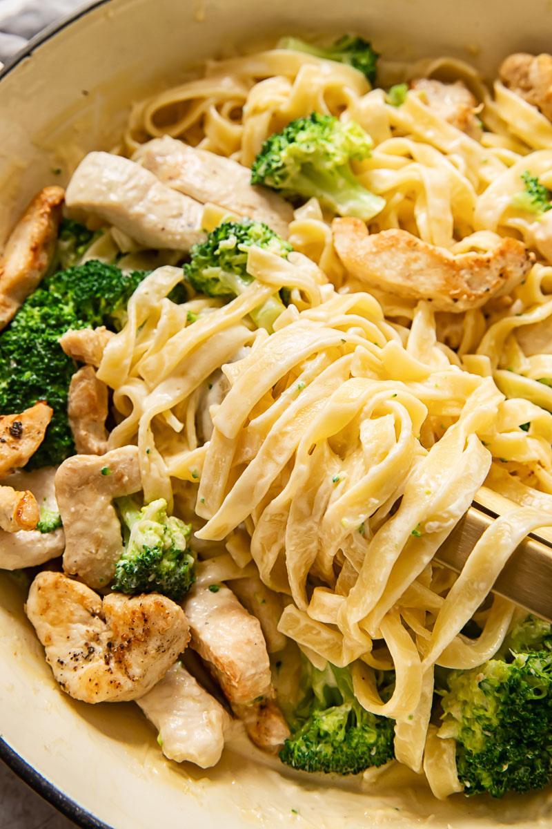 fettuccine in a creamy sauce with chicken and broccoli in a pan