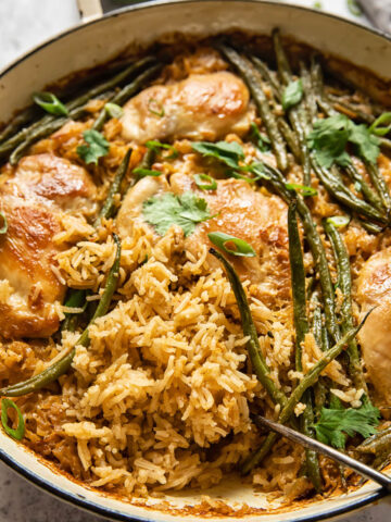 chicken and rice with green beans in white pan