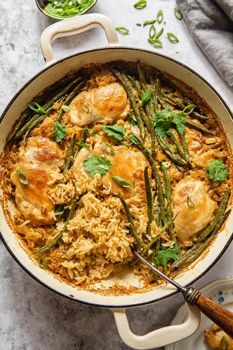 top down view of chicken and rice with green beans in a white pan