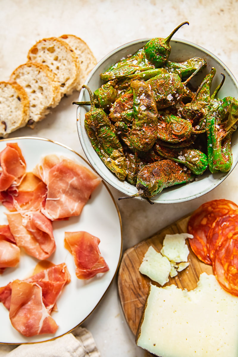 top down view of padron peppers, Serrano ham, chorizo and cheese on a board