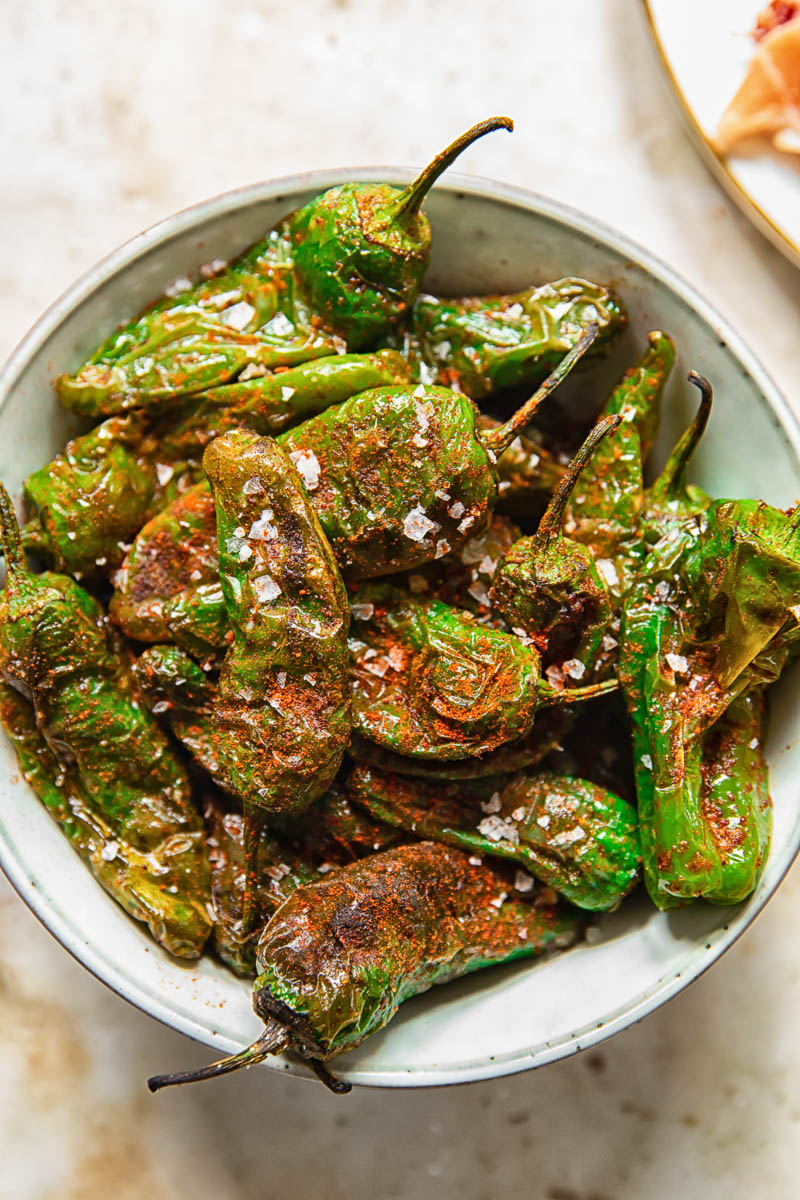 top down view of cooked padron peppers in a bowl