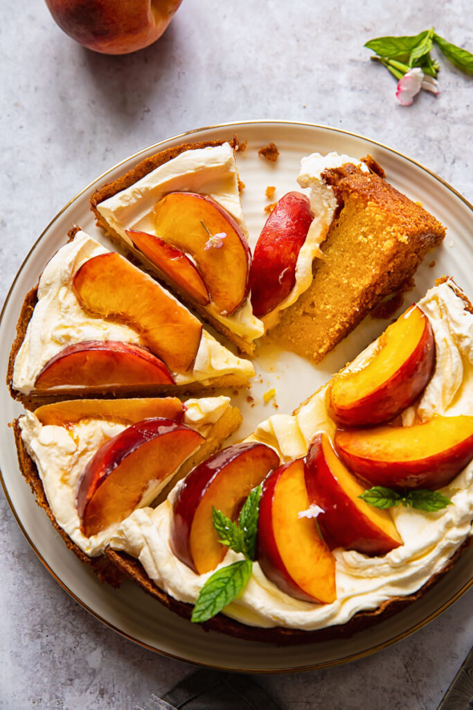 top down view of cake topped with whipped cream and sliced peaches