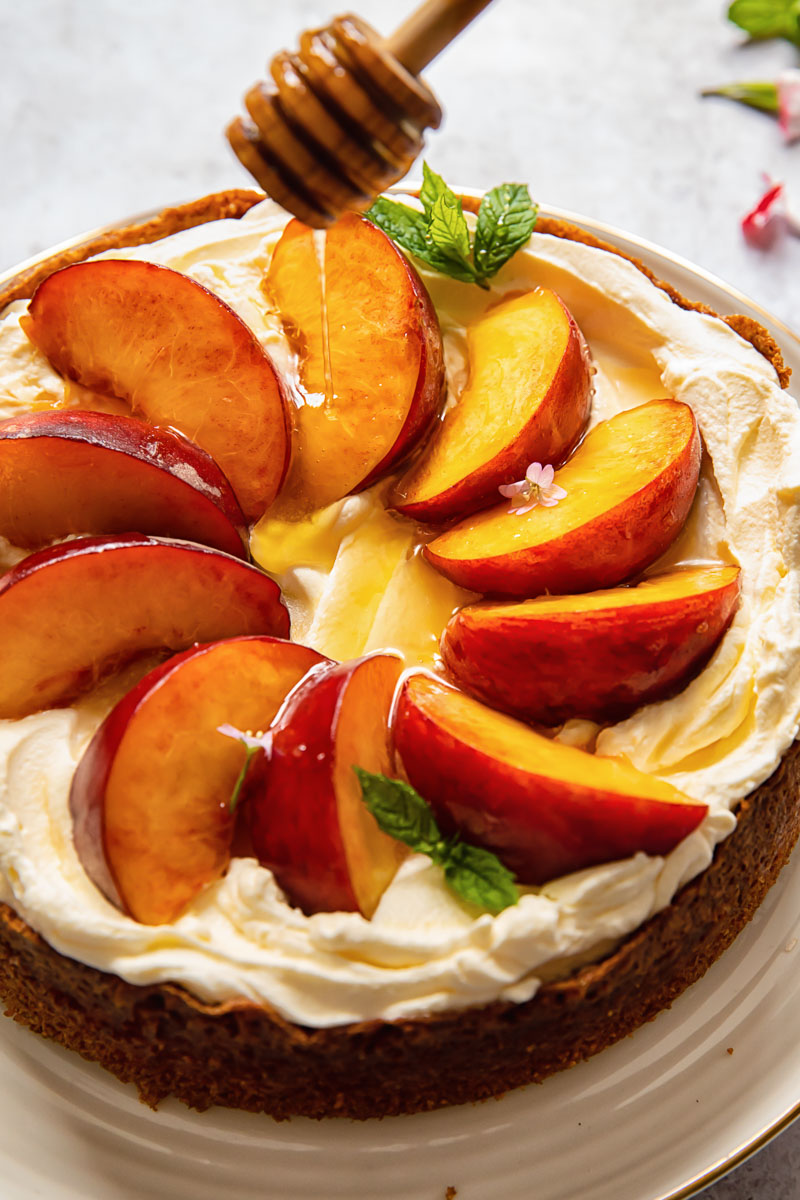 cake topped with whipped cream and sliced peaches, then drizzled with honey