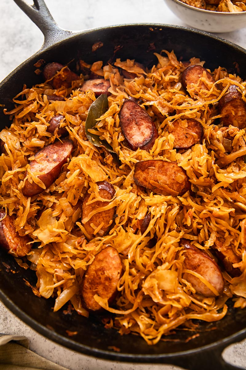 braised sauerkraut with tomatoes and kielbasa in a skillet