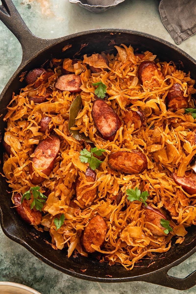 top down view of kielbasa and sauerkraut in a frying pan