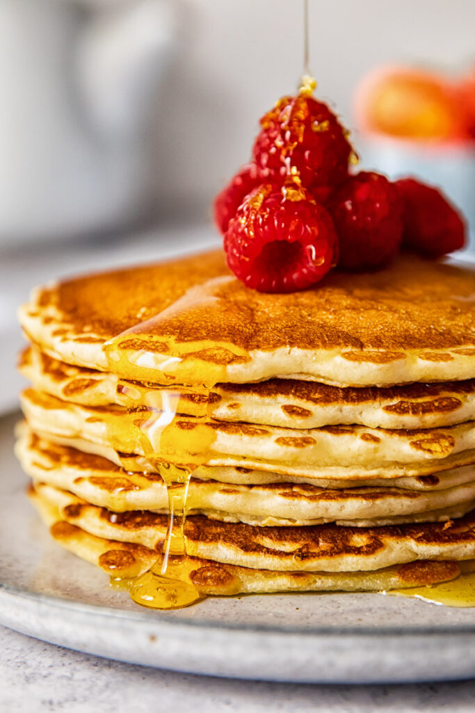 side view of a pancake stack topped with Maple syrup and raspberries